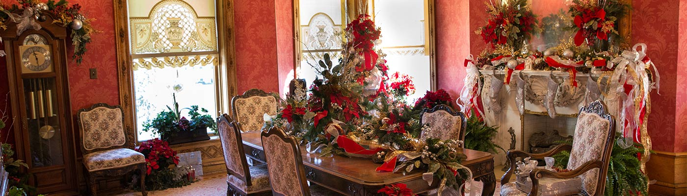 Christmas in the Castle in a dinning room with fireplace.