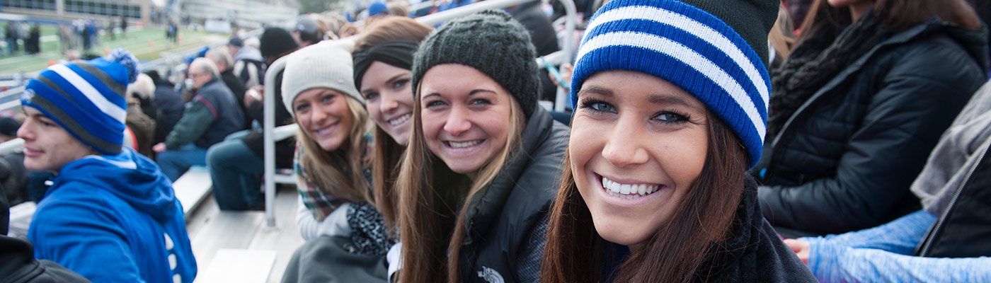 Female students in the stands at a football game cheering.